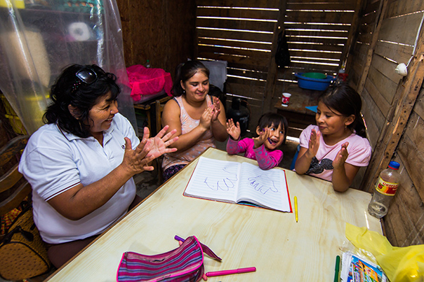 Community health worker Inela Espinoza teaches educational games to a family in their home.