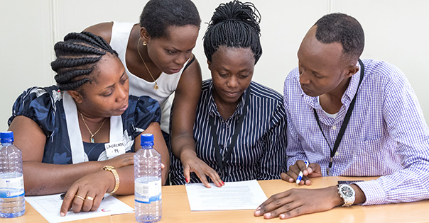 A group of UGHE students and faculty gather around a research article.