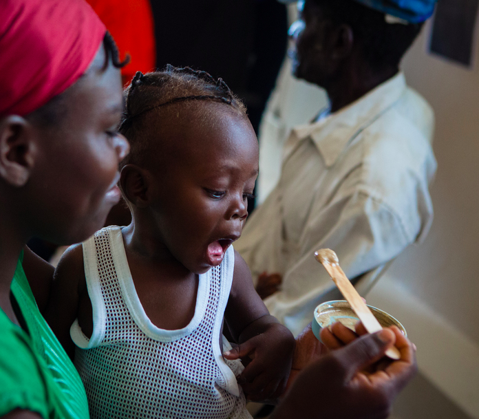 Oclène Davensky is fed a nutrient-rich peanut paste by his mother at the PIH-supported malnutrition clinic in Boucan Carré, Haiti.