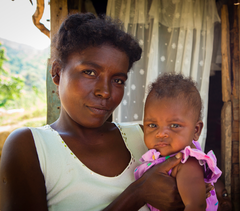 Gertha Morette holds baby Neleida, 3 months, outside of her home in Lascahobas, Haiti.