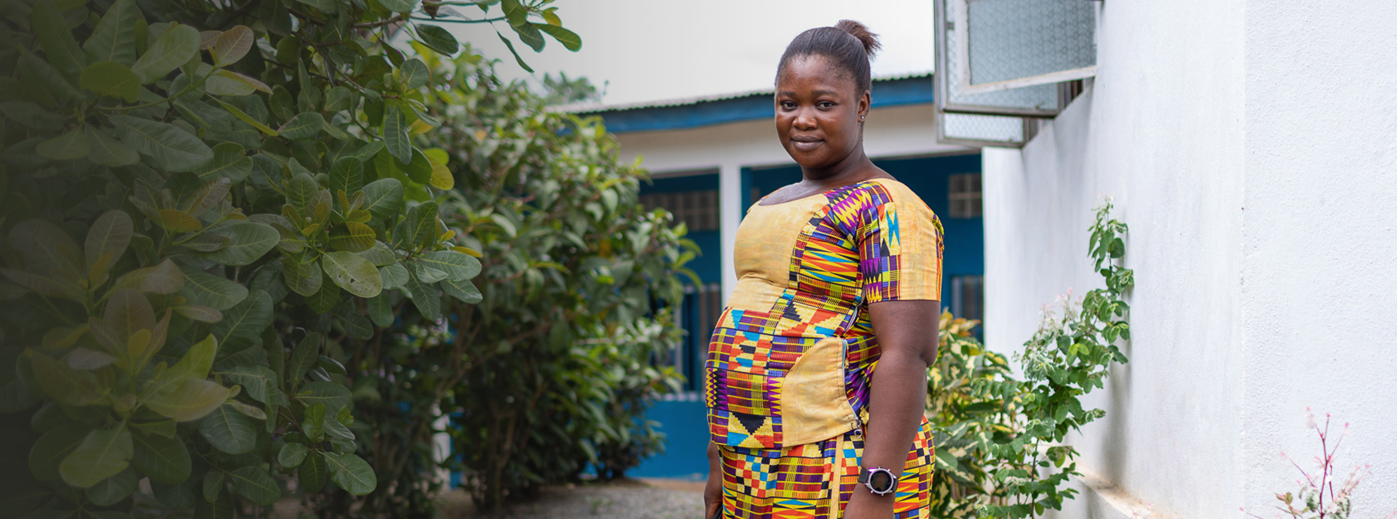 An expectant mother stands outside of a maternal waiting home in Sierra Leone.