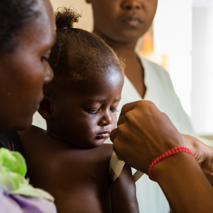 Child in Haiti has her arm measured as a test for malnutrition