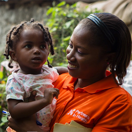 woman in pih shirt holding a young girl