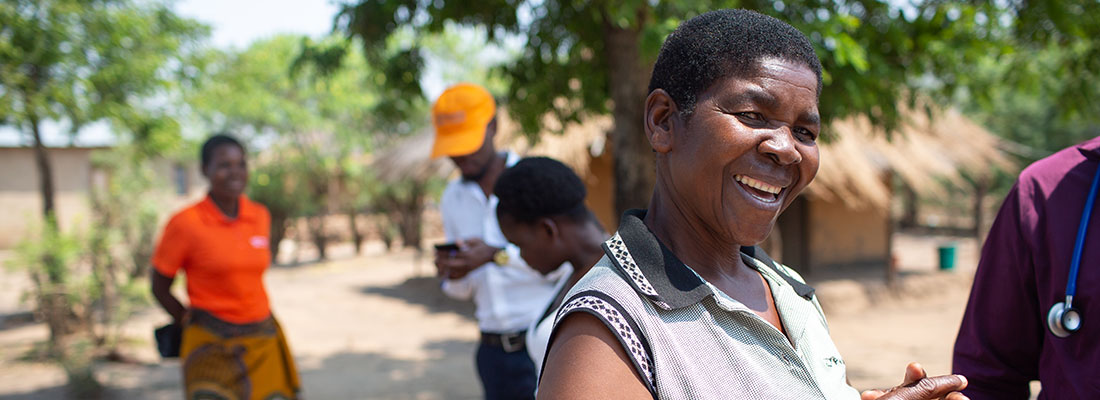 Rhoda Simba, a friend and fellow CHW, warmly greets the home visit group as they walk back to the PIH vehicle.
