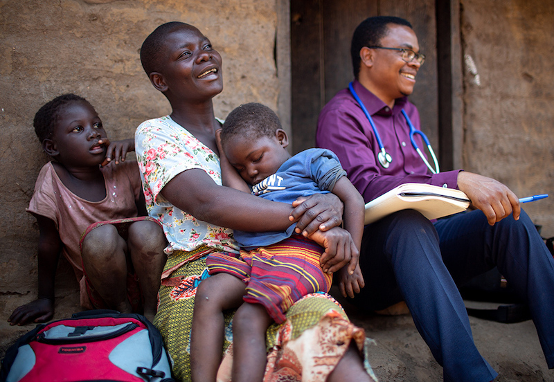 woman sits with her children and shares a laugh with doctor on step of house
