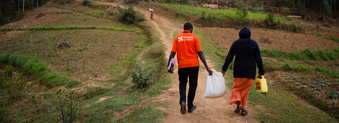 a oncology program coordinator and social worker walk to a patient's home in Burera District, Rwanda. They are carrying a food support package.