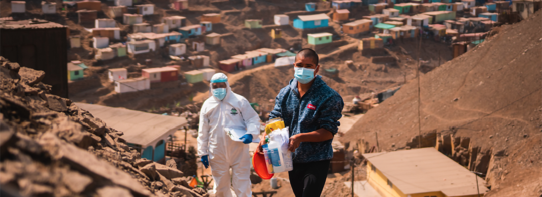 two healthcare workers with healthcare supplies walking up path in Peru