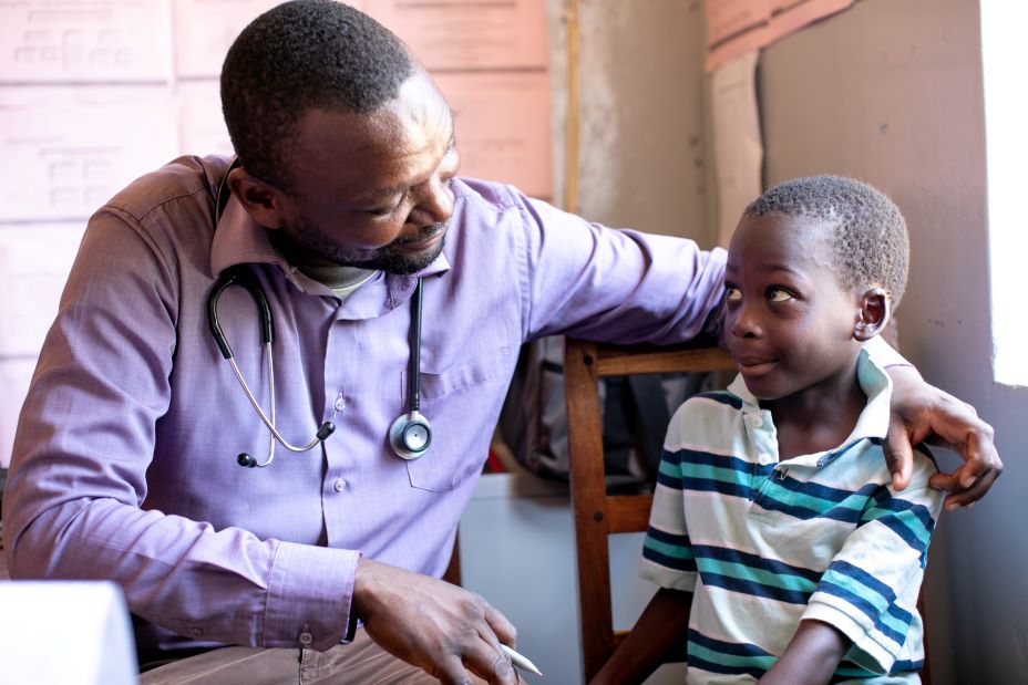 At PIH-supported Lisungwi Community Hospital in Neno, Malawi, Clinical Officer Medson Boti sits with 7-year-old Kevini Jamu, who receives free, specialized care and medicines for sickle cell disease.