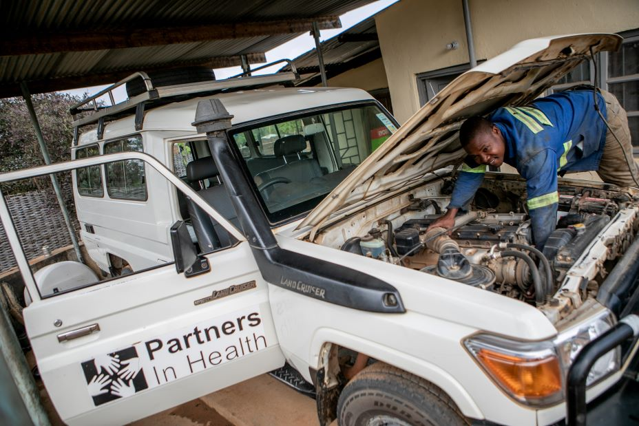 William Owen, a driver and mechanic for PIH in Malawi, checks on the health of one of his team's SUVs.