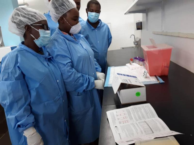 Lab technicians for Zanmi Lasante examine COVID-19 tests