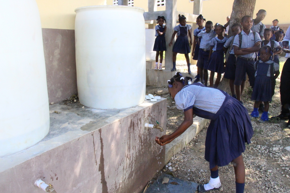 student washes her hands after recess at school in Mirebalais, Haiti