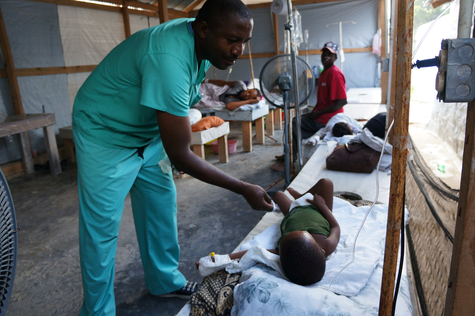 doctor provides care to cholera patient in Mirebalais, Haiti