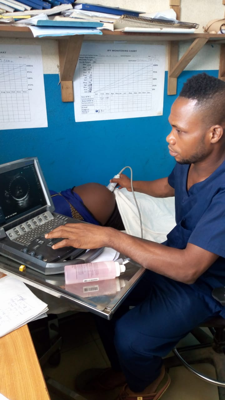 male nurse midwife performs ultrasound for pregnant patient at clinic in Liberia