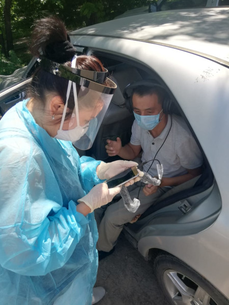 Dr. Merey Otepbergenova conducts a hearing test with a patient in her car