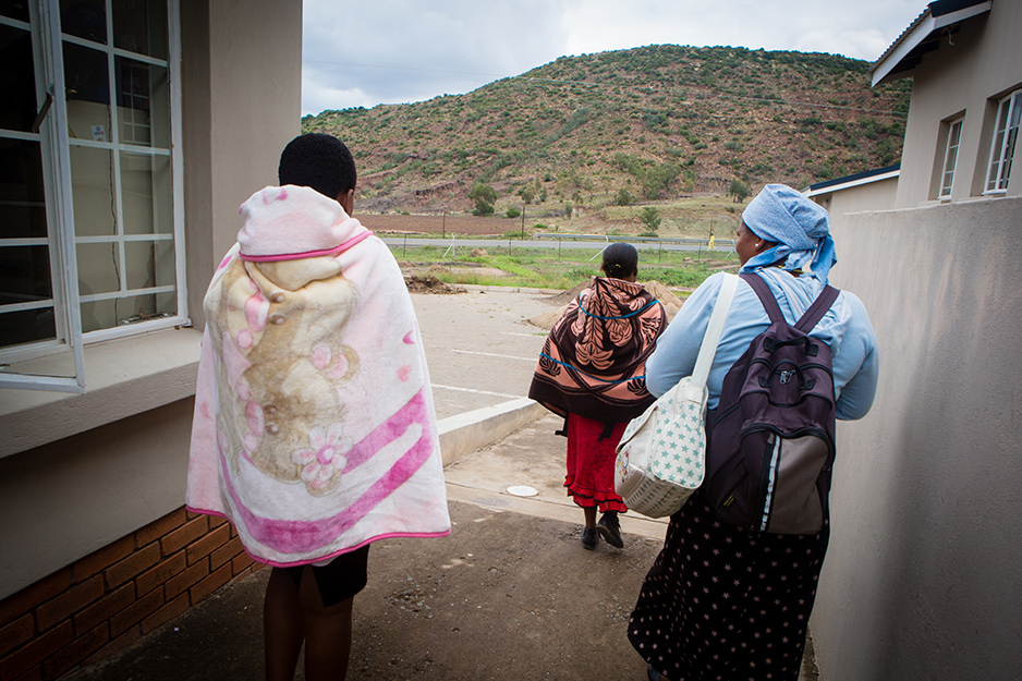 Matsebo (left) leaves the health center with her village health worker Malerato Tsoelesa (center), and her other son.