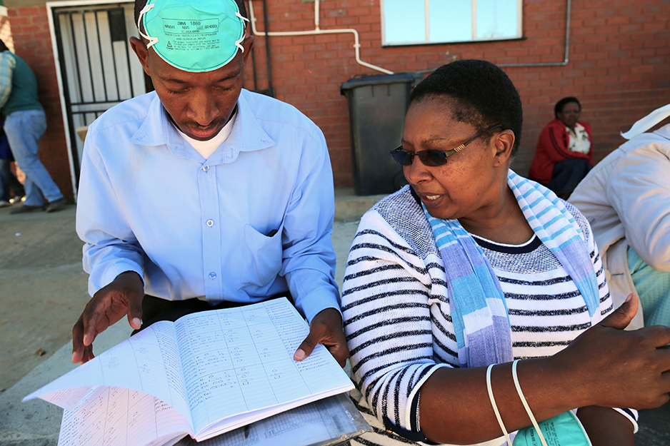 seko Motšela (left) and Nurse Likhapha Ntlamelle scan a patient's medication log, which records the daily doses of drugs needed to treat MDR-TB, in Maseru, Lesotho, in March 2016.
