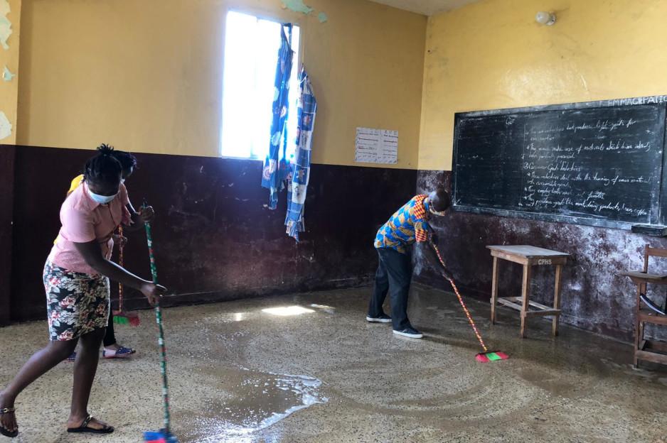 PIH staff in Liberia clean up a classroom for conversion into a COVID-19 care facility