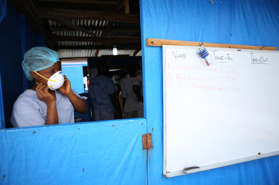 A clinician prepares before entering an Ebola treatment unit in Liberia