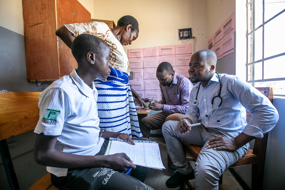 Kerefasi Wiliyamu, 14, talks with clinical officers at the Advanced NCD Clinic