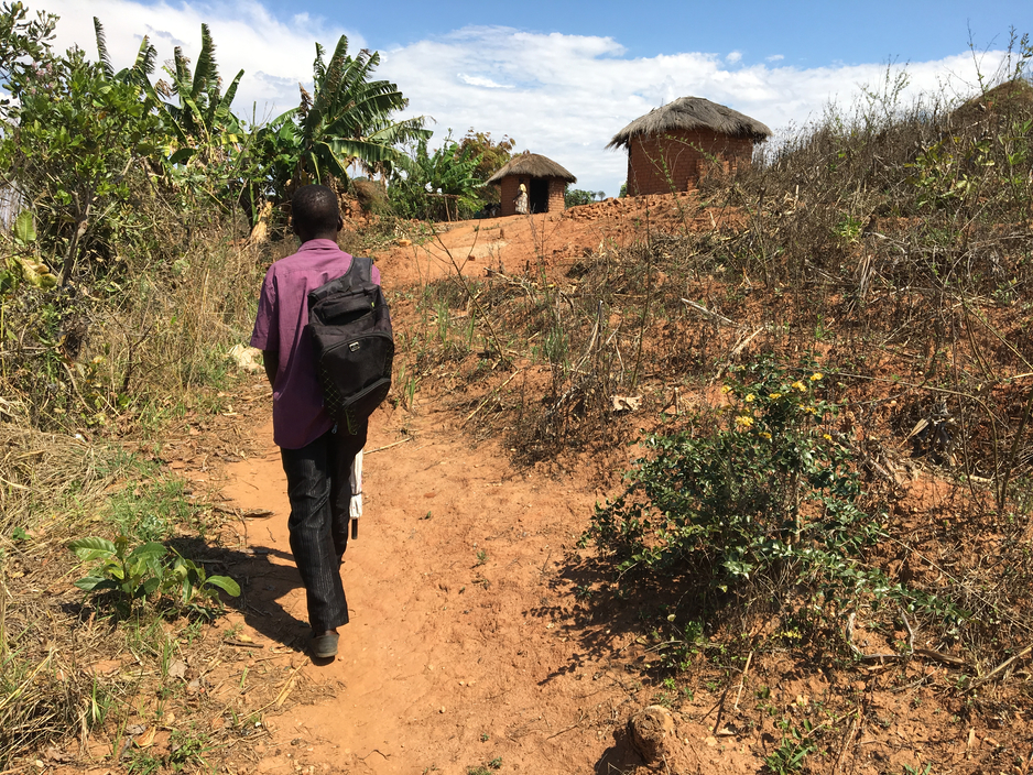 Health worker Silvester Dambe walks to Keredonia Wilfred's home