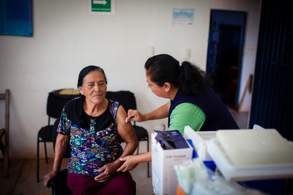 a nurse in rural Mexico provides a flu vaccination to her elderly relative