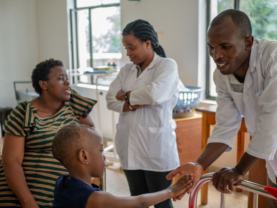 Olivier Habimanaand (right) and Esperance Benemariya, oncology nurse educators at PIH-supported Butaro District Hospital in Rwanda, meet with Keza Solange, who is being treated for leukemia, and her mother in the pediatric ward.