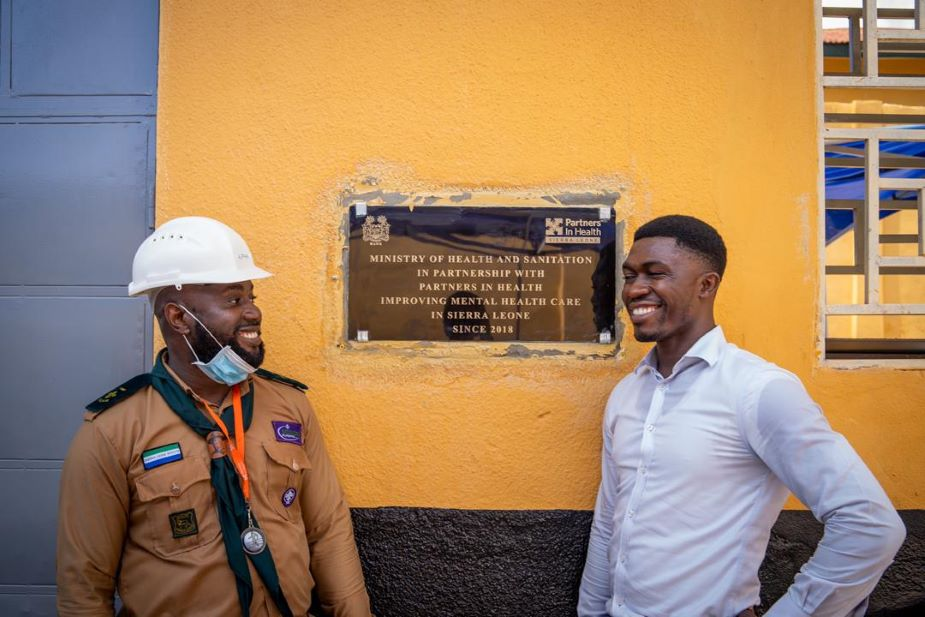 "Sheriff and Alpha Sesay, who supervised the infrastructure remodel of SLPTH, pose with another plaque at the hospital. It reads: ""Ministry of Health and Sanitation in partnership with Partners In Health, improving mental health care in Sierra Leone since 2018."""