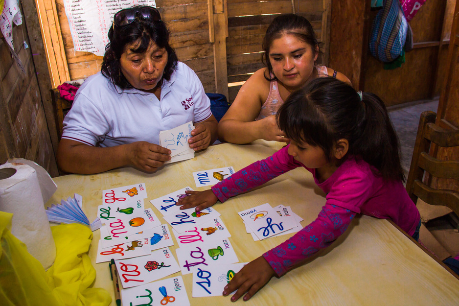community health worker guides a family through interactive play in Peru