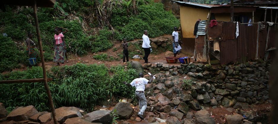 PIH staff visit the home of Ebola survivors in Sierra Leone, in 2014