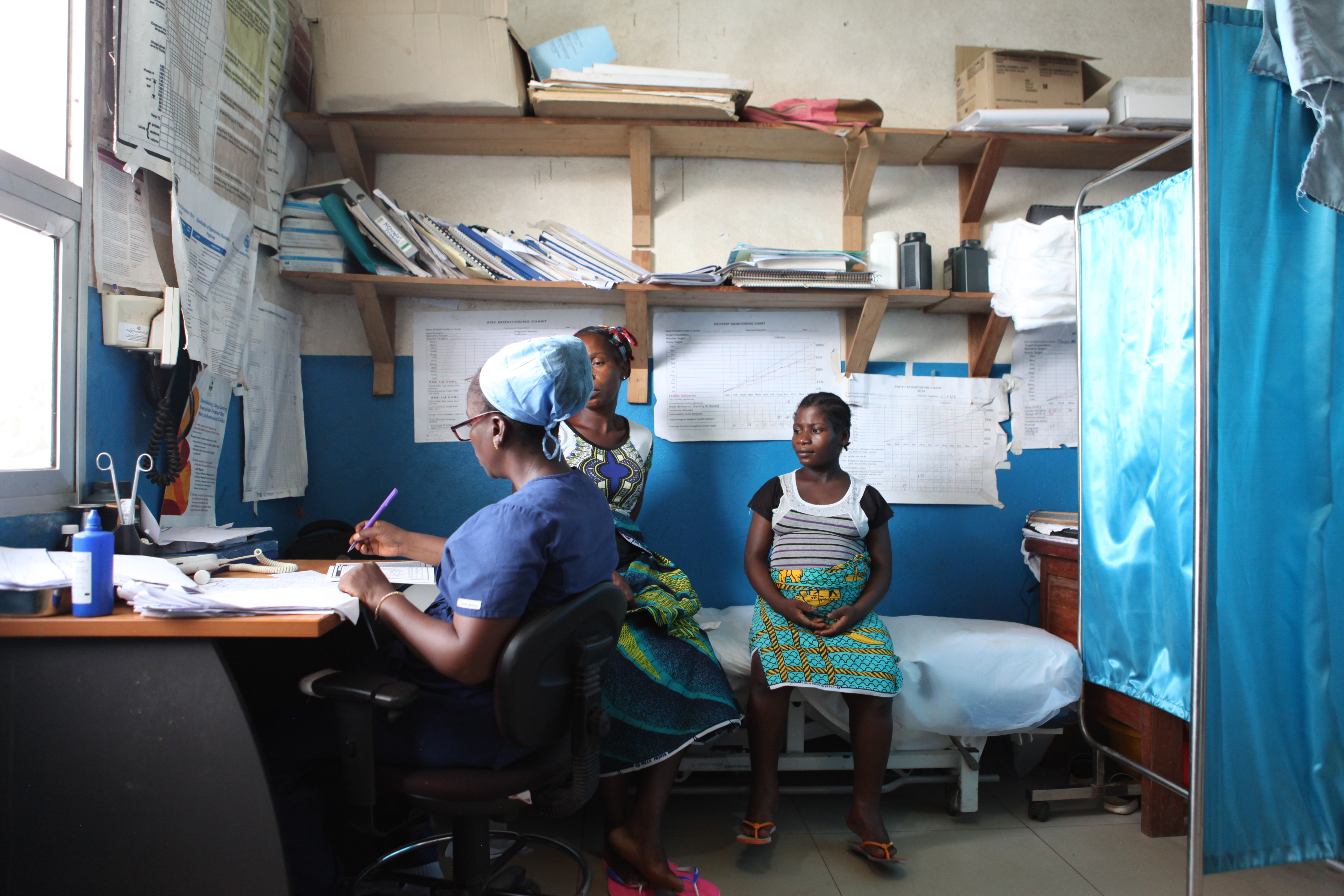 patient sits for prenatal checkup with midwife in Liberia