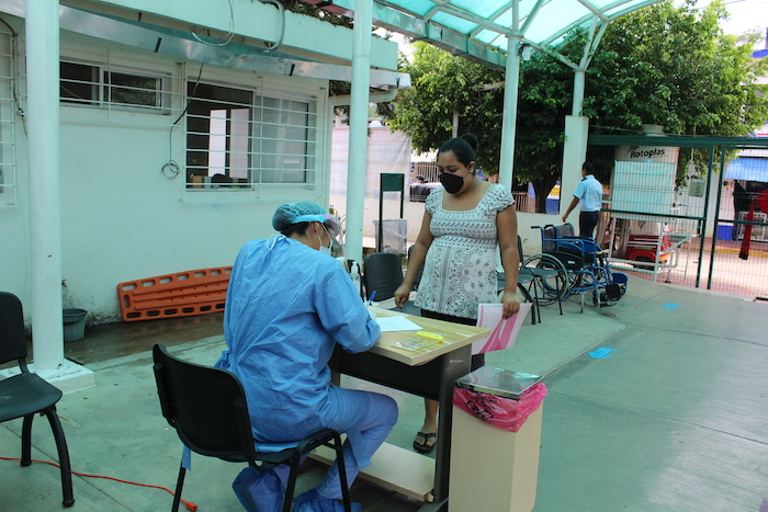 caregiver checking in patients for covid test