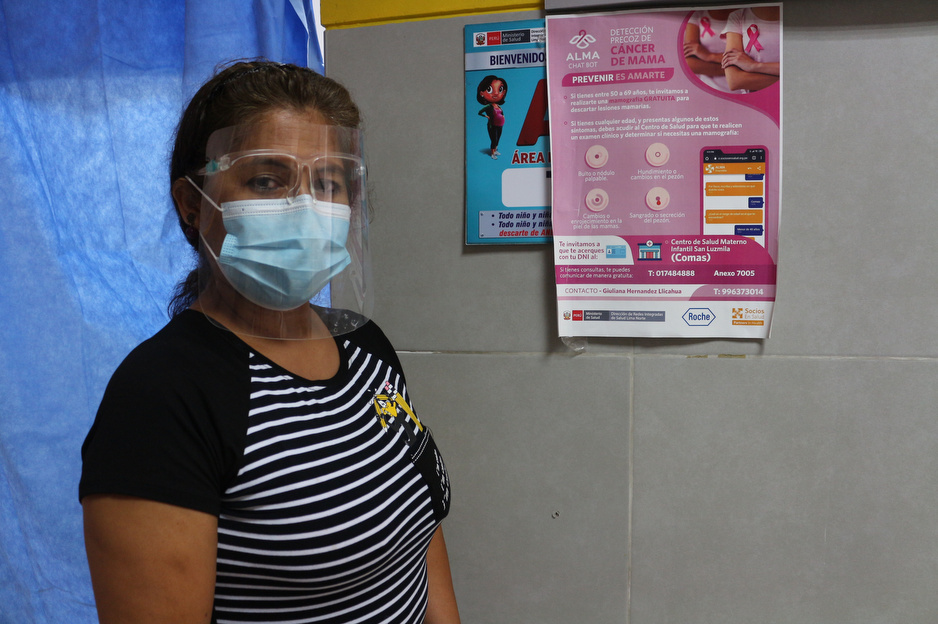 A patient stands next to a poster with information about breast cancer.