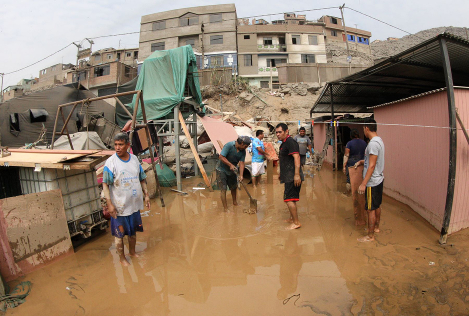People in Peru stand knee-deep in water after a flood tore through Carabayllo, an impoverished neighborhood near Lima.