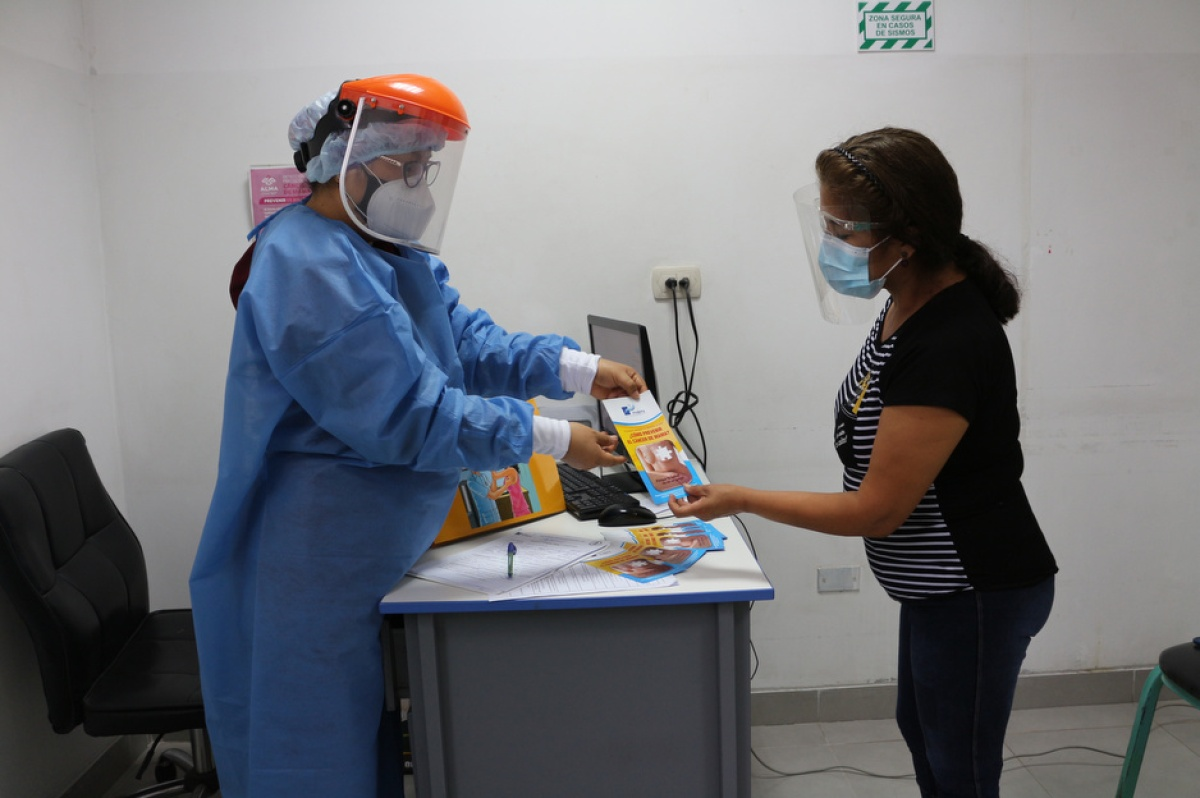 A doctor in personal protective equipment gives a patient information about breast cancer.
