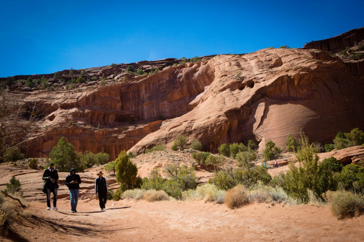 Three people walk in Canyon de Chelly in Navajo Nation, where hundreds of abandoned uranium mines continue to pollute the environment.