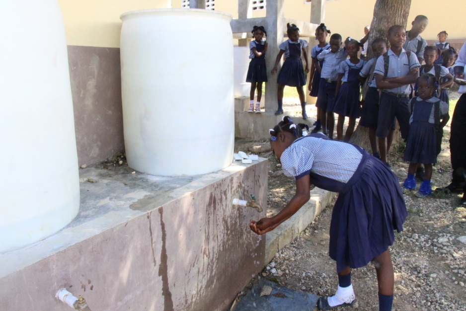 a girl washes her hands with soap and water at a school in Mirebalais, Haiti