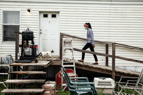 Maria Plata walks to a resident's door during COVID-19 education efforts