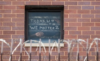 At Cook County Jail in Illinois, where COVID-19 has run rampant through prisons, incarcerated people hold a sign up to a window that says thank you, we matter too.