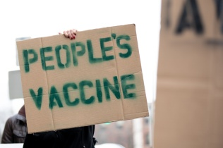 A protester holds a sign that says People's Vaccine