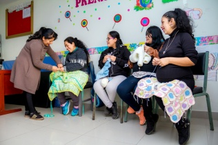 In Peru, mothers sit in a semicircle with knitted blankets and clothes on their laps as an instructor helps them.
