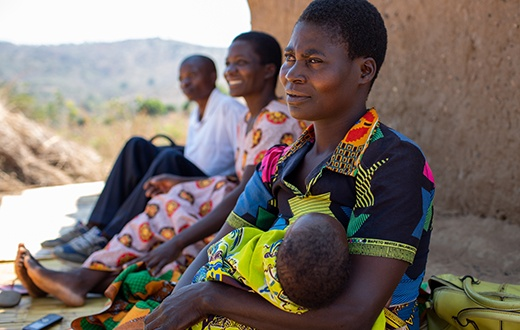 Agnes sits with her son, Ulemu, outside her home in Malawi.