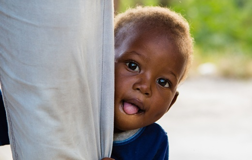 Lovenyou, a malnutrition patient, peeks out from his mother's legs outside their home in Haiti.