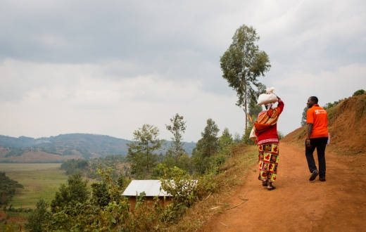 Jean Bosco Bigirimana, right, on the way to a home visit in Rwanda
