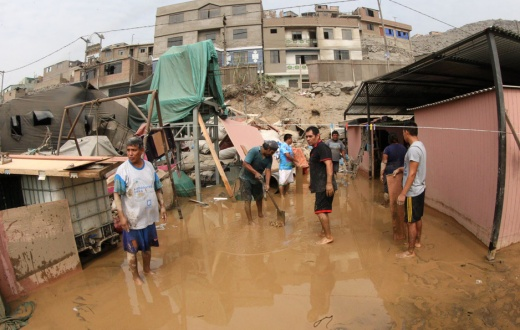 neighbors clear streets following massive floods in Lima, Peru