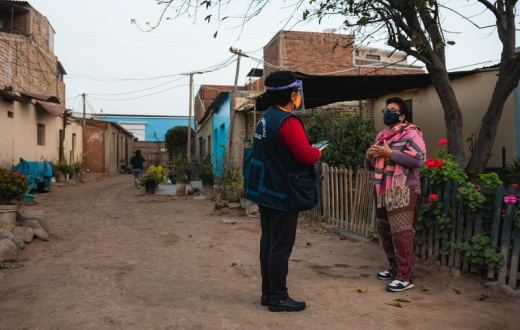 A staff member with Socios En Salud, as PIH is known in Peru, does a door-to-door mental health screening with a patient after a chatbot app connected them.