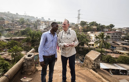 Paul Farmer stands on the Tengeh Town Bridge with Ibrahim Kamara in Freetown, Sierra Leone in 2015.