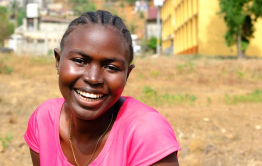 Saffiatu Sesay received care for tuberculosis at Lakka Government Hospital in Sierra Leone. She smiles for the camera and wears a pink shirt.
