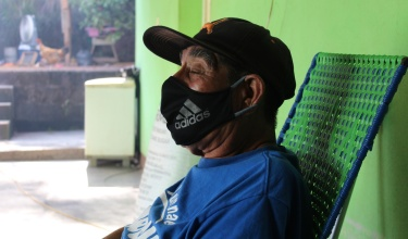 elderly patient sits on his front porch at home in Chiapas, Mexico. He wears a face mask.