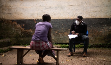 A PIH community health worker wearing a mask speaks to a patient from six feet away.