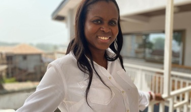 Vicky Reed, director of nursing for PIH Sierra Leone, poses for a photo in a white shirt on a balcony.